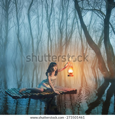 Woman with lantern floating on the lake in the misty forest in rustic white dress. Beautiful fairy tale. - stock photo