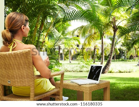 Woman with laptop computer in the tropical garden. Vacation. - stock photo