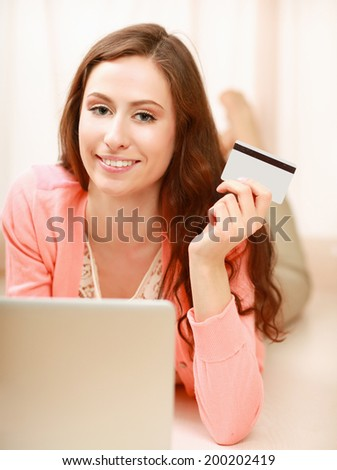 Woman with laptop lying on the floor and holding a credit card