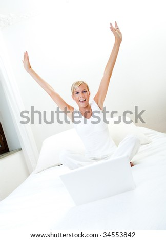 Woman with laptop on bed - stock photo