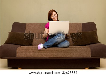 Woman with laptop on sofa - stock photo