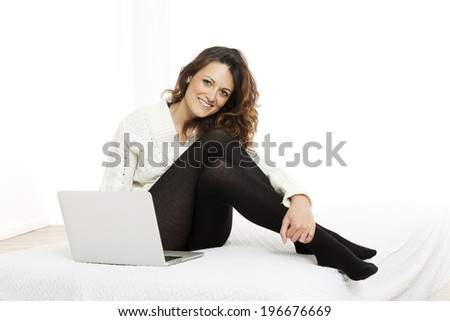 woman with laptop on white sheet in her bed at home - stock photo