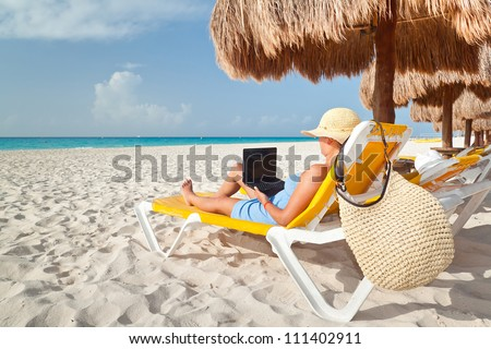 Woman with laptop relaxing on the deckchair at the Caribbean sea - stock photo