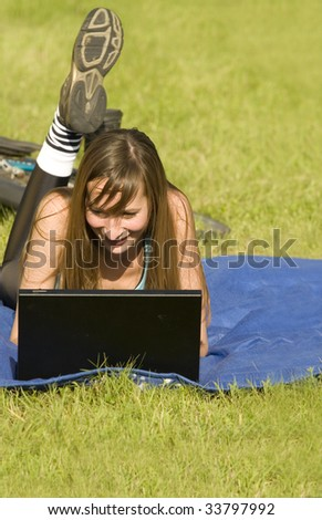 woman with laptop relaxing on the grass