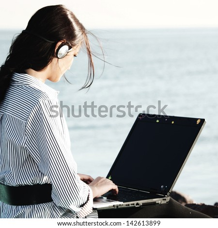 woman with laptop sea background - stock photo