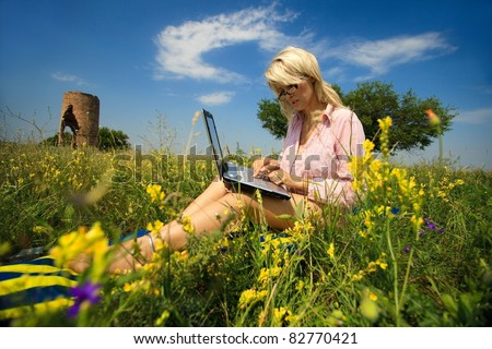 Woman with laptop sitting on blanket - stock photo