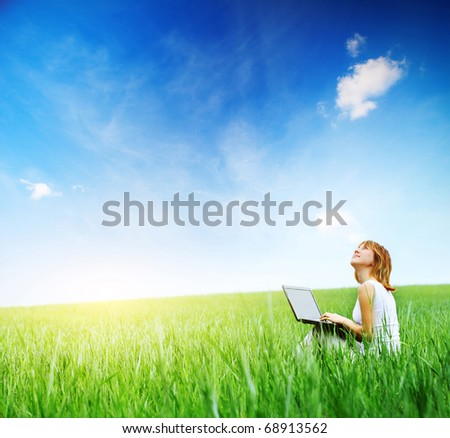 Woman with laptop sitting on green meadow and looking to a sky - stock photo