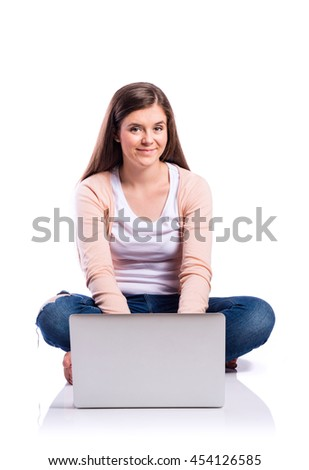 Woman with laptop sitting on the floor, studio shot, isolated - stock photo