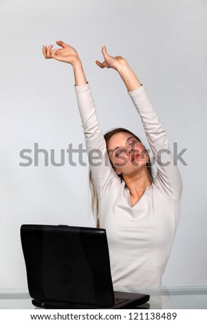 Woman with laptop stretching - stock photo
