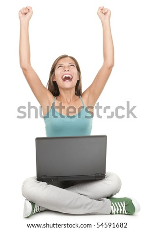 Woman with laptop winning with success. Celebrating sitting cross legged on the floor - isolated on white background.