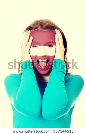 Woman with Latvia flag painted on face. - stock photo