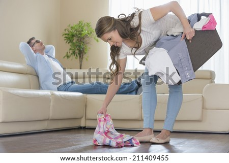 Woman with laundry basket picking clothes while man relaxing on sofa in background - stock photo