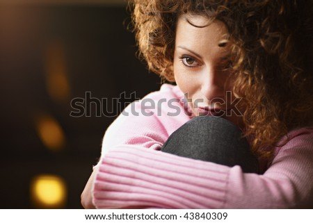 woman with legs drawn, looking away. Copy space - stock photo