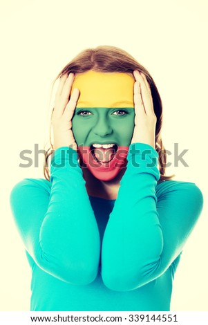 Woman with Lithuania flag painted on face. - stock photo