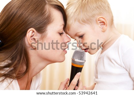 woman with little boy singing indoor - stock photo