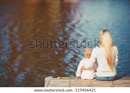 Woman with little daughter sitting near water turned back - stock photo