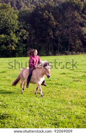 woman with little horse - horseback riding on paddock