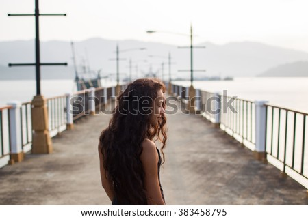Woman with long black hair walking on empty bridge in the morning