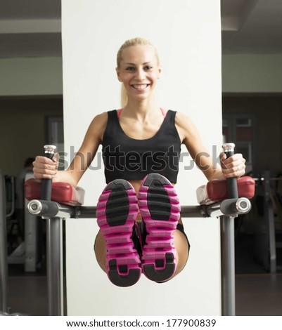 Woman with long blond hair using a leg press machine in a fitness club Focus on snickers Copy space for inscription - stock photo