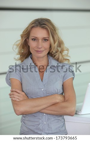 Woman with long blonde hair, arms folded - stock photo