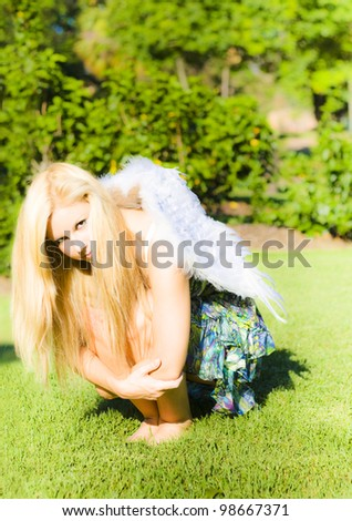 Woman with long blonde hair squatting arms around her knees, with feather wings on her back in a broken wings concept - stock photo