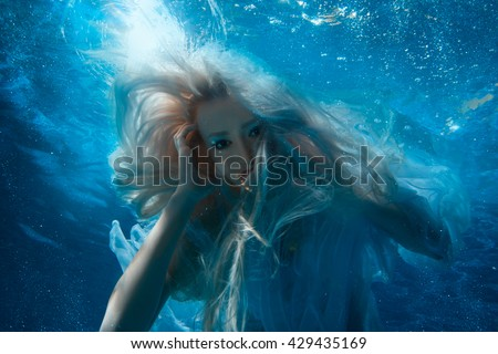 Woman with long blonde hair under the water, it looks like a mermaid. - stock photo