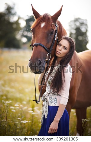 Woman with long brown hair and her lovely big brown horse.