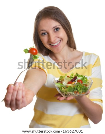 Woman with long brown hair eating salad - stock photo