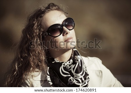 Woman with long curly hairs against a nature background - stock photo