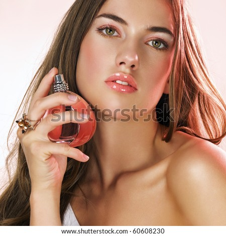 Woman with long hair applying perfume on her hair - stock photo