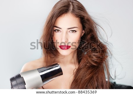 woman with long hair holding blow dryer - stock photo