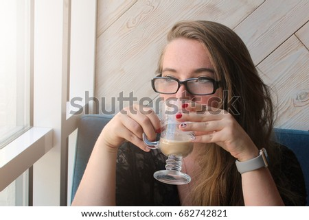 woman with long hair is drinking latte