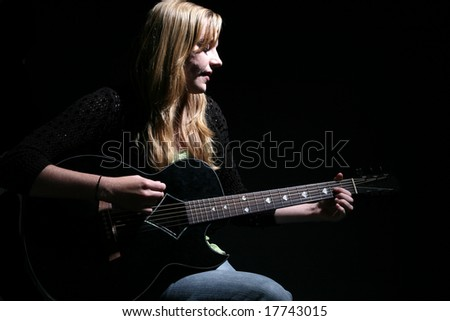woman with long hair playing guitar and singing - stock photo