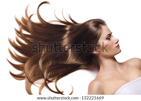 woman with long healthy hair lying on a white background