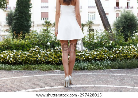 Woman with long legs going to hotel in summer dress, outdoor - stock photo