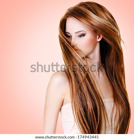 Woman with  long straight hairs over pink background - stock photo