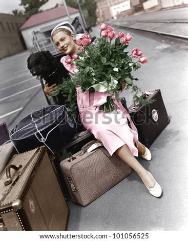 Woman with luggage flowers and dog - stock photo