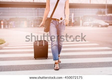 Woman with luggage passes through pedestrian crossing near airport
