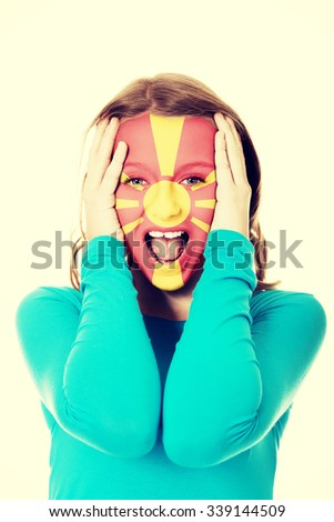 Woman with Macedonia flag painted on face. - stock photo