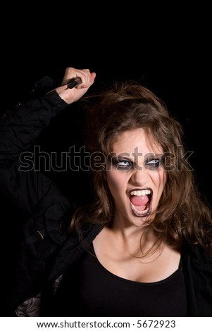 Woman with mad look in her face and big knife - stock photo