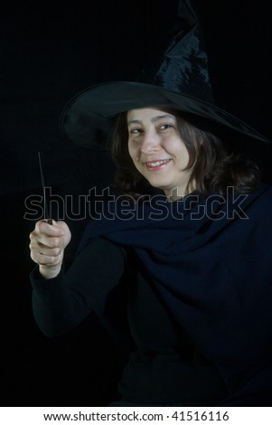 woman with magic wand on black background - stock photo