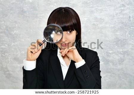woman with magnifying glass isolated on a gray background - stock photo
