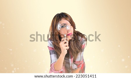 Woman with magnifying glass over ocher background - stock photo