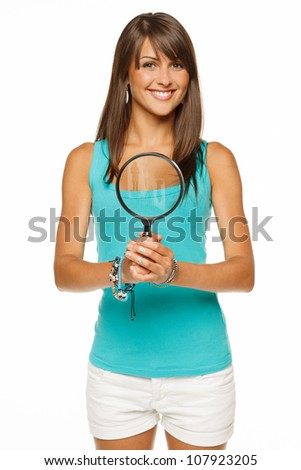 Woman with magnifying glass over white background - stock photo