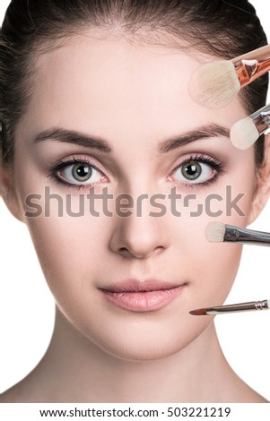 Woman with make-up brushes near face