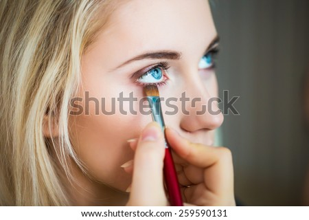 Woman with makeup brush - stock photo
