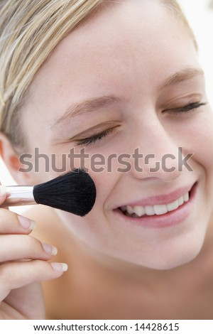 Woman with makeup brush smiling - stock photo