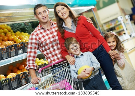 woman with man and child choosing melon fruit during shopping at vegetable supermarket - stock photo