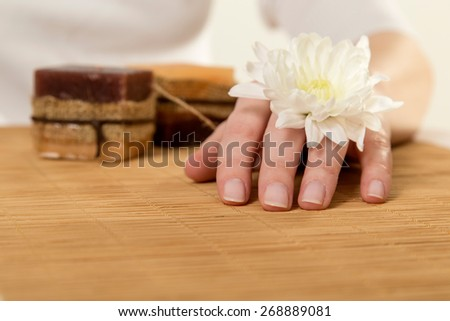 Woman with margarita flower on her hand in a nail salon - stock photo