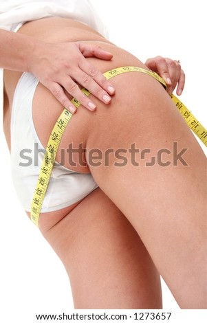 Woman with measuring tape looking for cellulite